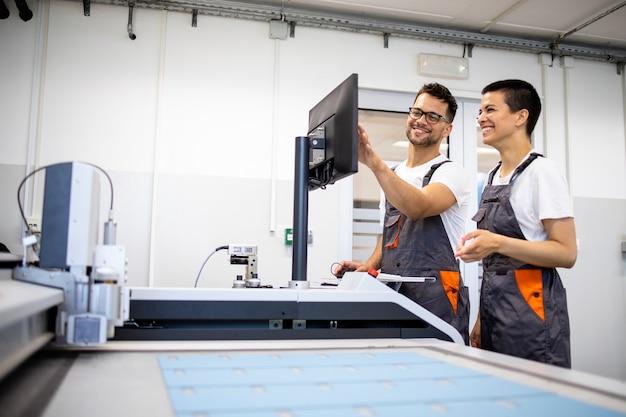 Ervaren technicus die nieuwe werknemer opleidt om cnc-industriële machine in de fabriek te bedienen.