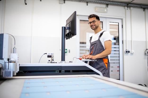 Ervaren technicus werknemer die cnc industriële machine bedient in de fabriek.