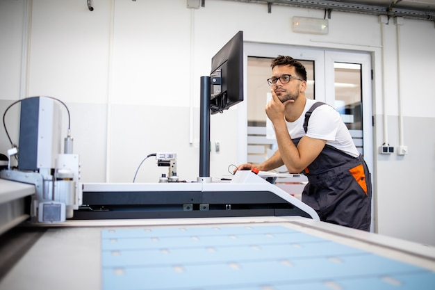 Ervaren technicusarbeider die probleem op cnc industriële machine probeert op te lossen.