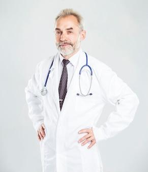 Ervaren therapeut met een stethoscoop op lichte muur
