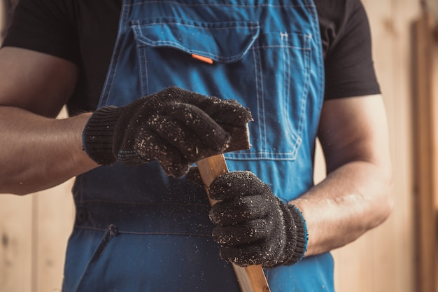 Ervaren timmerman in werkkleding en kleine bedrijfseigenaar die in houtbewerkingsworkshop werkt
