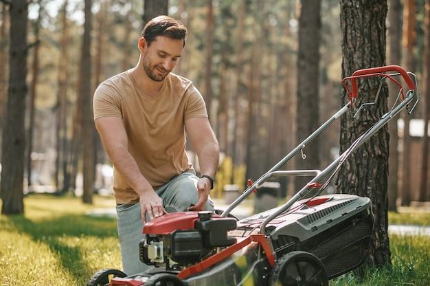 Ervaren tuinman gehurkt bij grasmaaier