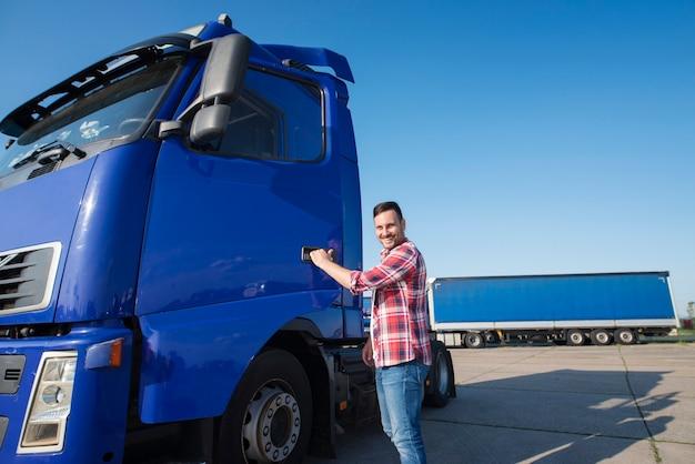 Ervaren vrachtwagenchauffeur van middelbare leeftijd die het voertuig betreedt