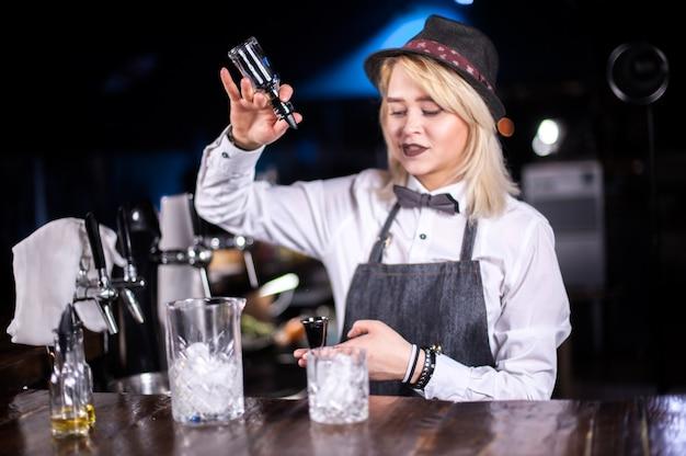 Ervaren vrouw barmeisje versiert kleurrijk brouwsel in de nachtclub