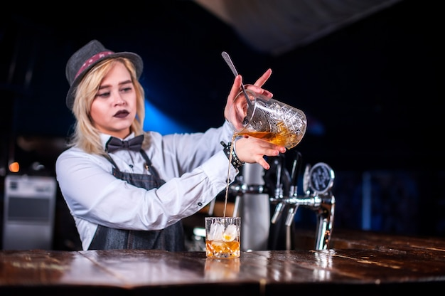 Ervaren vrouw bartending verse alcoholische drank gieten in de glazen in de nachtclub
