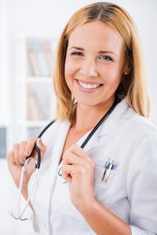Ervaren vrouwelijke arts. gelukkig vrouwelijke arts in wit uniform camera kijken en glimlachen