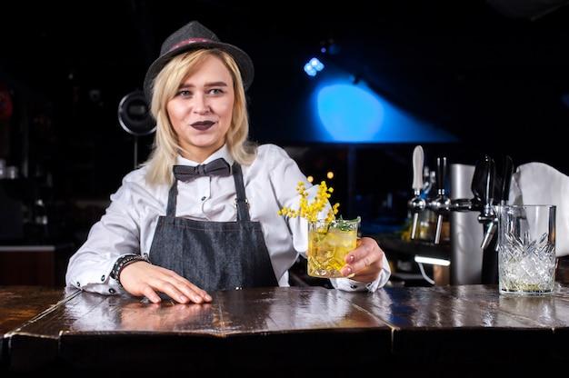 Ervaren vrouwelijke barman maakt een show die een cocktail achter de bar maakt