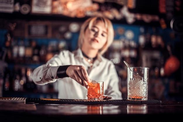 Ervaren vrouwenbarkeeper demonstreert zijn professionele vaardigheden in de nachtclub