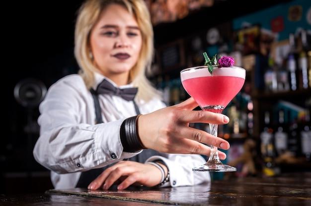 Ervaren vrouwentapster demonstreert het proces van het maken van een cocktail