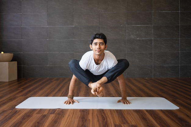 Ervaren yogi die vuurvlieg doet, stelt variatie in de sportschool
