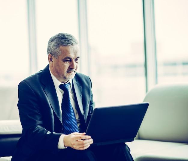 Ervaren zakenman die aan laptop werkt die op bank in ap . zit