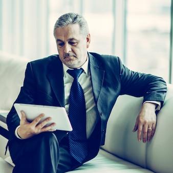 Ervaren zakenman die naar het scherm van een digitale tafel kijkt