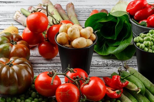 Erwten en aardappelen met paprika, tomaten, asperges, paksoi, groene peulen, wortelen in mini-emmers op houten muur, hoge hoekmening.
