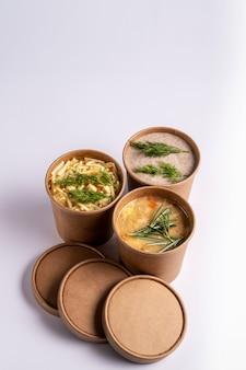 Erwten en champignons en kippensoep in papieren wegwerpbekers voor afhaalmaaltijden