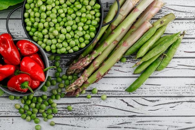Erwten in een pan met paprika, asperges, groene peulen bovenaanzicht op een houten muur
