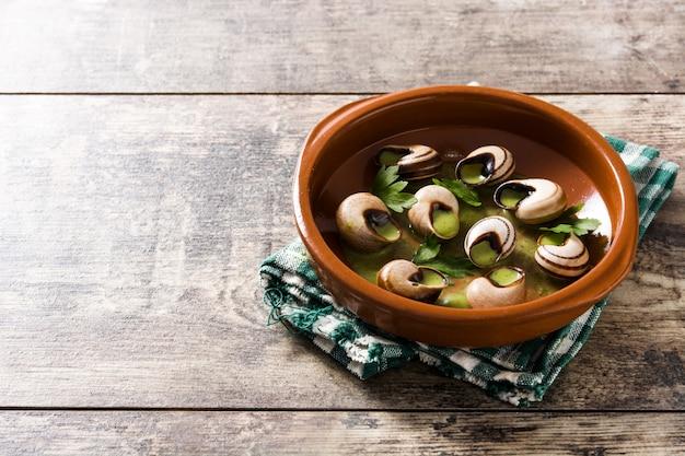 Escargots de bourgogne in bruine kom op houten tafel, kopie ruimte