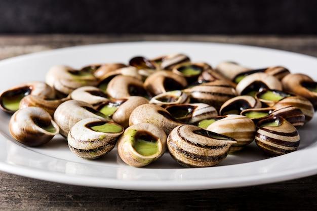 Escargots de bourgogne. slakken met kruiden en knoflookboter op een plaat