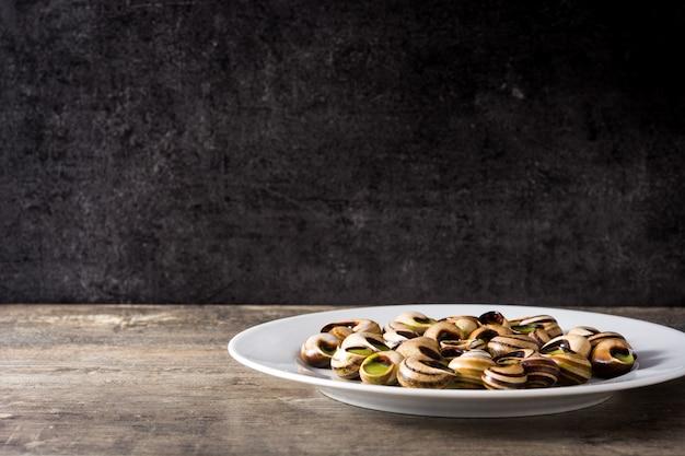 Escargots de bourgogne slakken met kruiden en kruidenboter op een bord