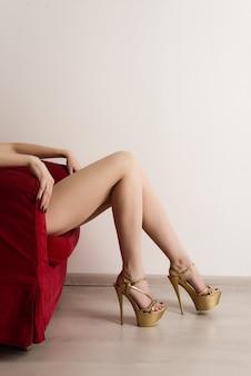 Escort, prostituee of sugar babe liggend op rode stoel met lange benen en sexy gouden hoge hakken.