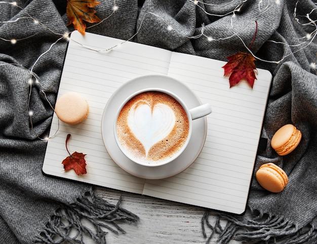 Esdoornbladeren, notitieboekje, koffiekopje en sjaal. herfst of winter concept. plat lag, bovenaanzicht