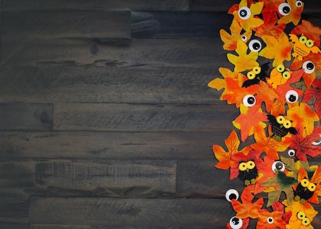 Esdoornbladeren van herfstkleuren en ogen die op houten bruine achtergrond met exemplaarruimte liggen halloween-tijd