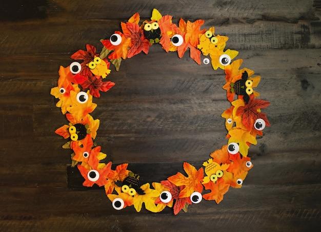 Esdoornbladeren van herfstkleuren en ogen liggen op houten bruine achtergrond met kopieerruimte halloween-tijd