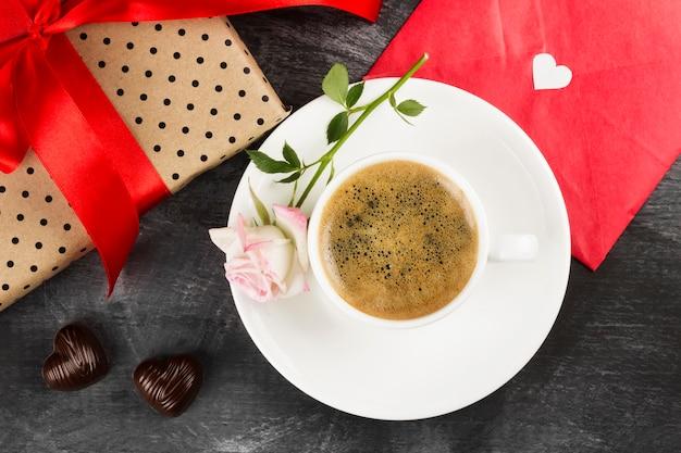 Espresso koffie in een witte kop, een roze roos, een geschenk met bureaucratie en chocolaatjes op een donkere achtergrond. bovenaanzicht voedsel achtergrond