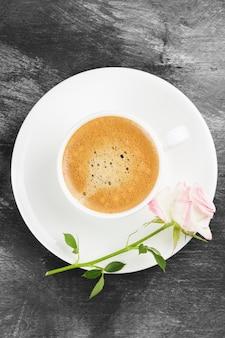 Espresso koffie in een witte kop, een roze roos en chocolaatjes op een donkere achtergrond. bovenaanzicht voedsel achtergrond.