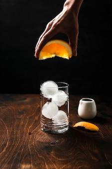 Espresso-tonic bereiden met sinaasappelsap. hand uit een wig sinaasappelsap in een longdrinkglas gevuld met ijsbollen.