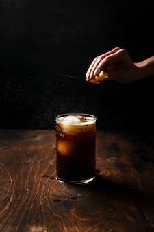 Espresso-tonic bereiden met sinaasappelsap. sinaasappelschiloliën uitpersen boven een longdrinkglas met een drankje.