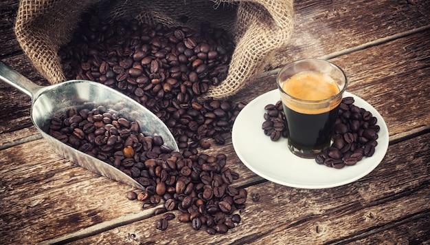 Espressokoffie in glaskop met koffiebonen.