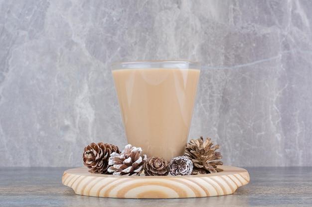 Espressokoffie met dennenappels op een houten bord. hoge kwaliteit foto