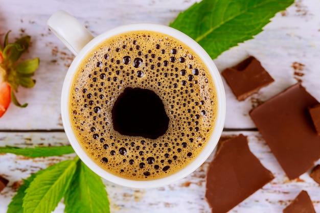 Espressokoffie met stukjes schuim, munt en chocolete