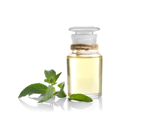 Essentiële aromaolie in glazen fles met verse muntblaadjes op witte achtergrond
