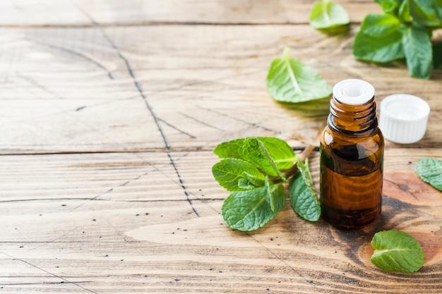 Essentiële aromaolie met pepermunt op houten achtergrond.