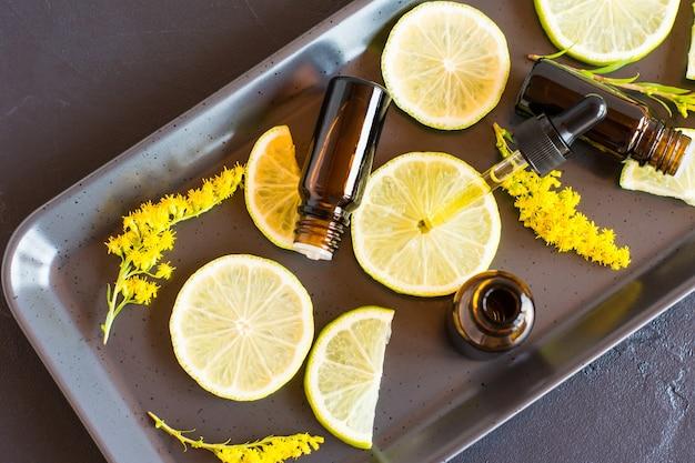 Essentiële aromatische olie met citrusvruchten op een zwarte achtergrond. het concept van schoonheid en huidverzorging van het gezicht en lichaam.