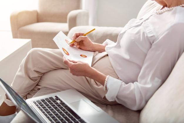 Essentiële correcties. de close-up van een sjiek geklede oudere vrouw die op de bank zit en de grafieken op de afdruk bestudeert en enkele correcties aanbrengt