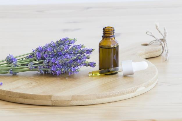 Essentiële lavendelolie in de fles met druppelaar op houten bureau. horizontaal close-up