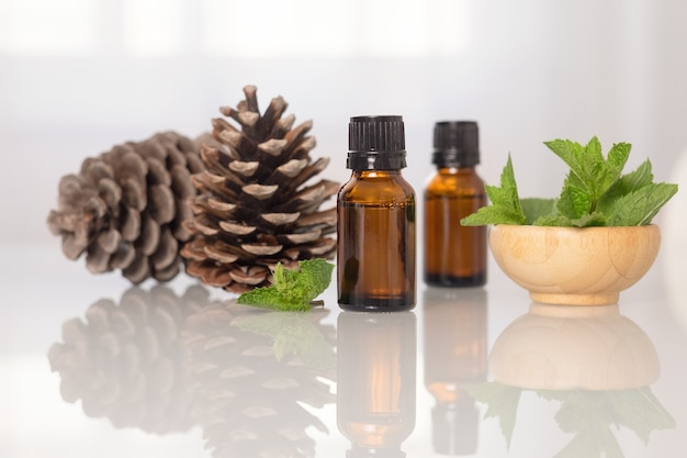 Essentiële olie van munt en dennen in kleine flesjes op een glazen tafel.