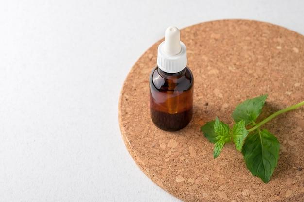 Essentiële olie van munt. muntblaadjes, olie in een kleine glazen fles. witte achtergrond