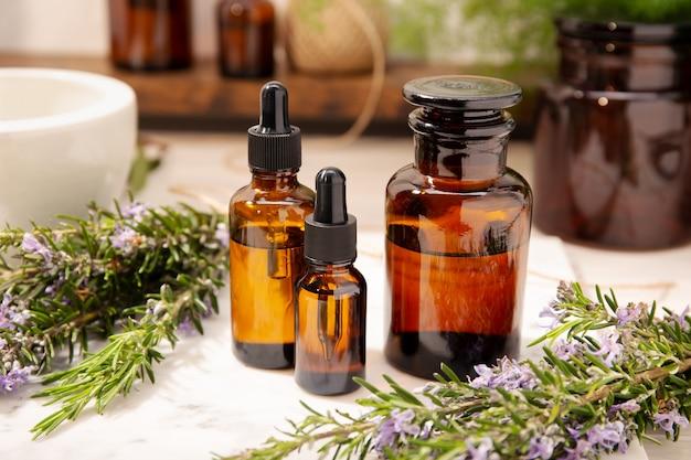 Essentiële olie van rozemarijn op vintage apothekersflessen. kruidenolie voor huidverzorging, aromatherapie en natuurlijke geneeskunde