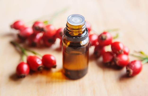 Essentiële olie van rozenbottelzaad in een klein flesje. selectieve aandacht.