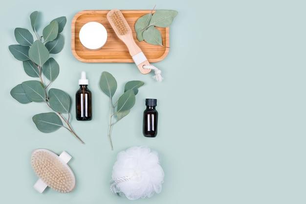Essentiële oliën, gezichtscrème container en massageborstels met natuurlijke eucalyptusbladeren op groene achtergrond