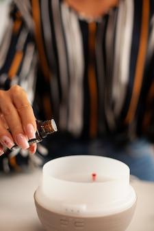 Essentiële oliën in diffuser gieten voor aromatherapie