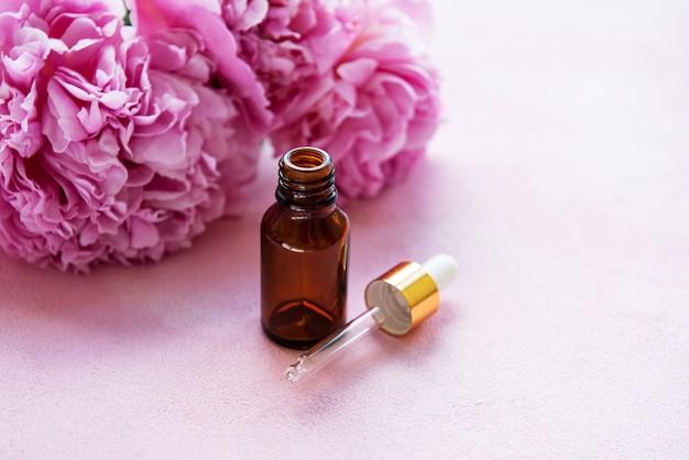 Essentiële oliën voor aromatherapie en roze pioenrozen