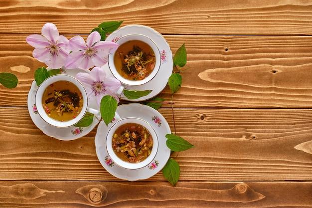 Esthetisch schot van kopjes thee met bloemen binnen op een houten tafel
