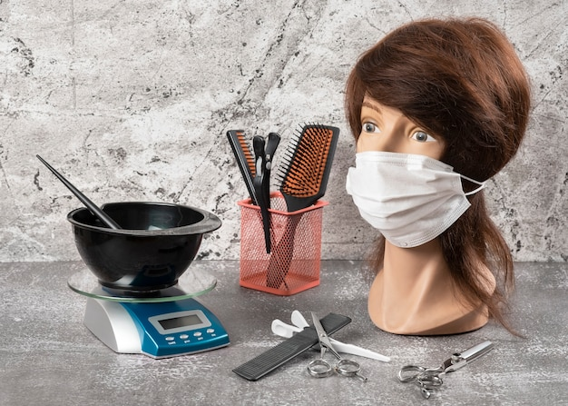 Etalagepop in maskergezicht, weegschaal en kom met penseel en kappersgereedschap