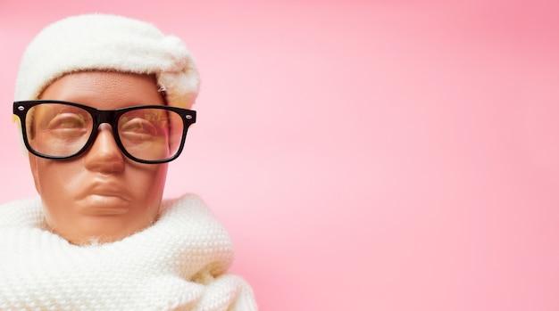 Etalagepop met bril en sjaal, kortingen op winterkleren en accessoires, op een roze achtergrond