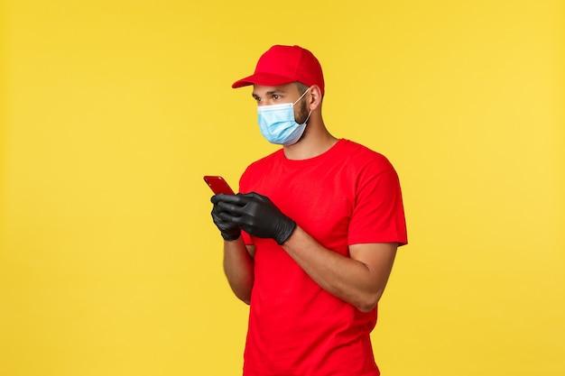 Eten bezorgen, bestellingen volgen, covid-19 en zelfquarantaineconcept. koerier of werknemer in rood uniform, medisch masker en handschoenen, smartphone gebruikend, naar links kijkend, klantadres zoeken om af te leveren