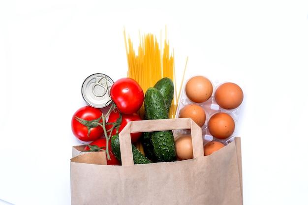 Eten bezorgen papieren zak met verse producten pasta blikvoer groenten boter eieren voedseldonaties